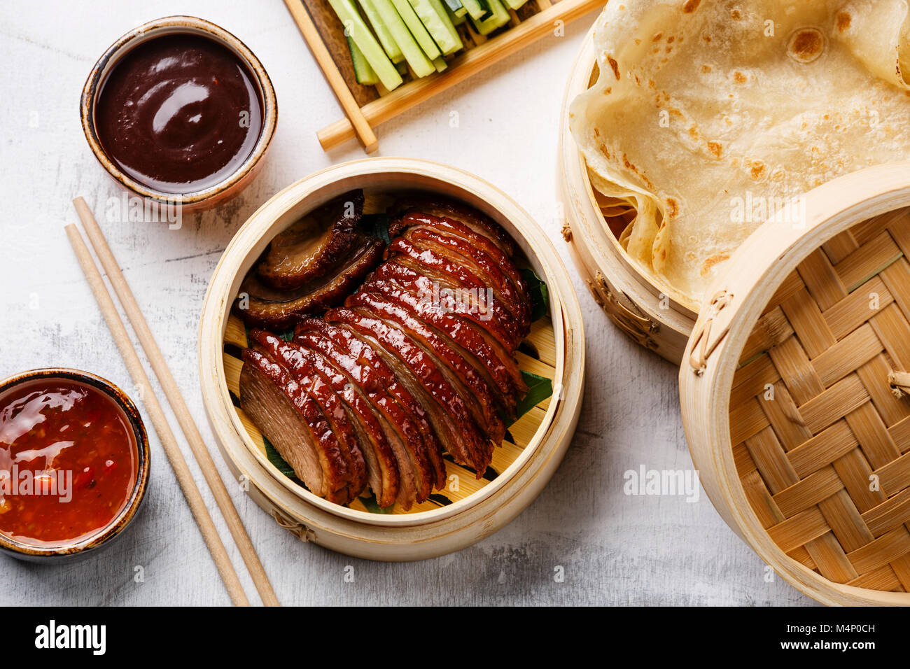 Sliced Peking Duck in bamboo steamer served with fresh cucumber, green onions, cilantro and roasted wheaten chinese - Stock Image