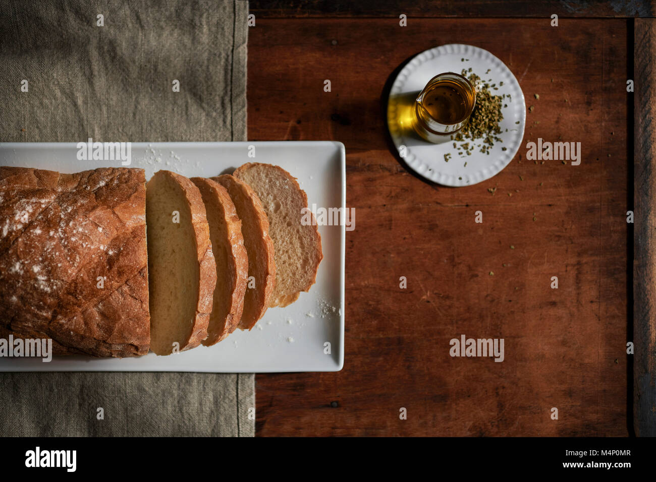 Loaf of rustic, white bread sliced on a white plate with oil and herbs nearby on a rich, wood tabletop with linen. - Stock Image