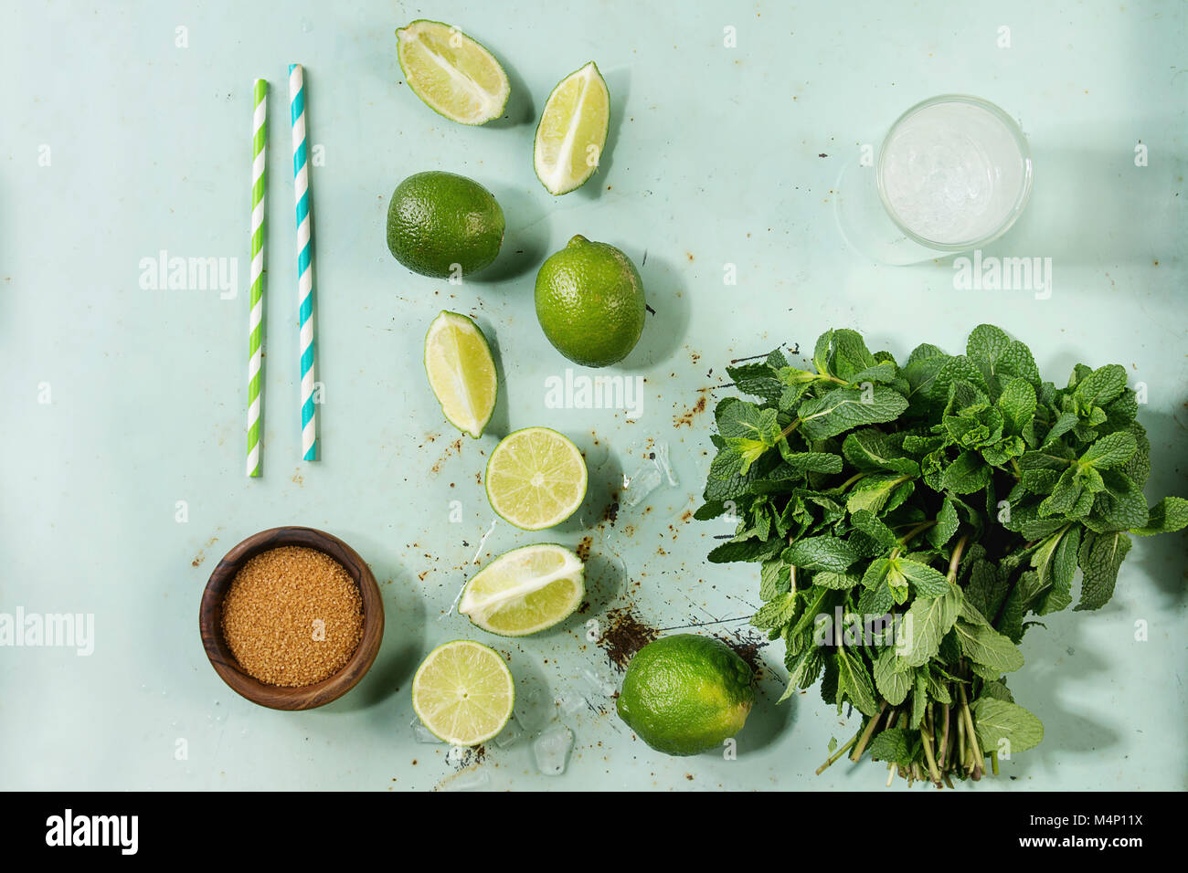 Ingredients for making mojito cocktail. Bundle of fresh mint, limes, brown sugar, crashed ice cubes, glass of soda - Stock Image