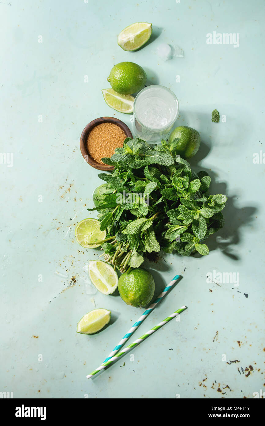 Ingredients for making mojito cocktail. Bundle of fresh mint, whole and sliced limes, brown sugar, crashed ice cubes, - Stock Image