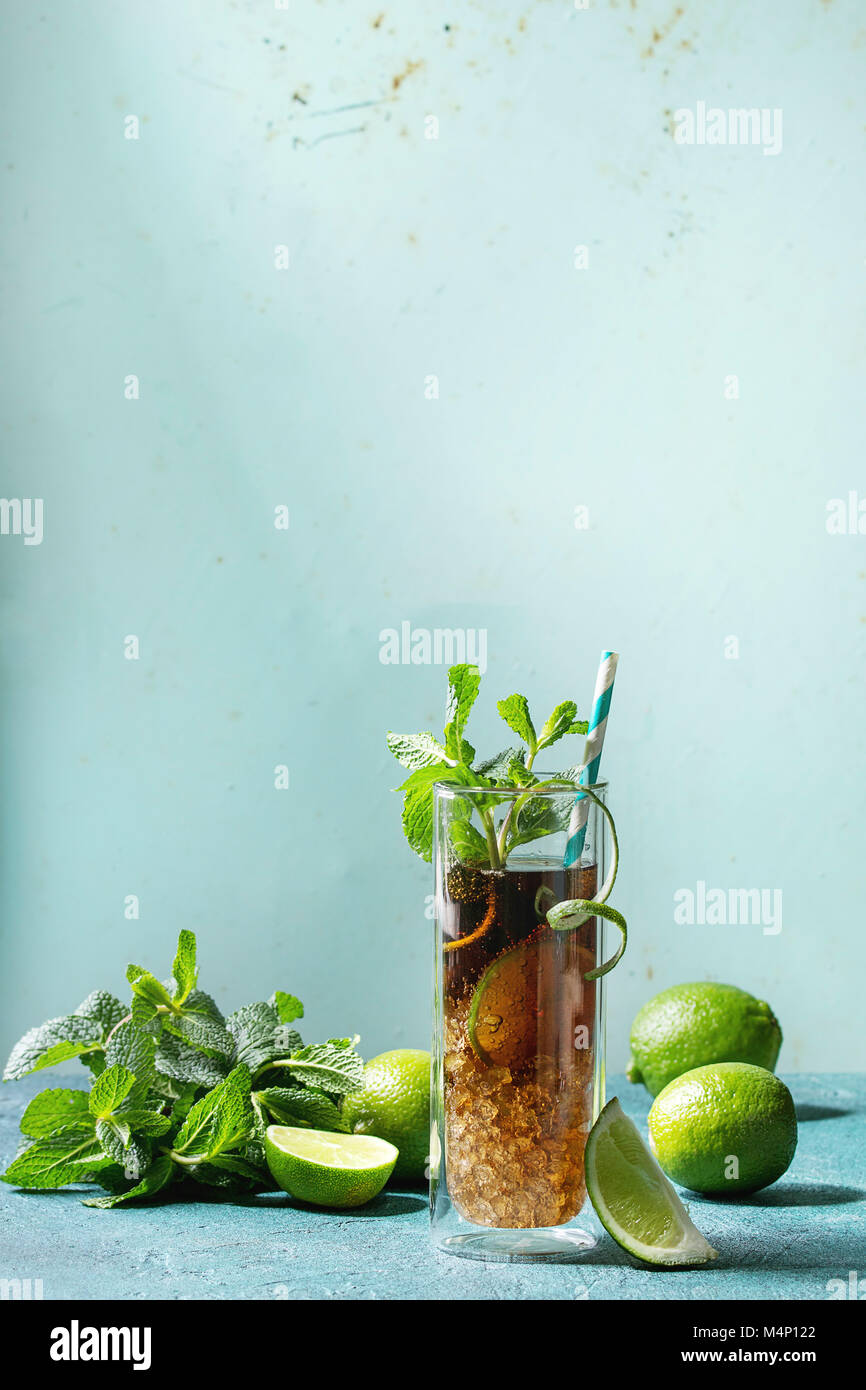 Glass of classic Cuba libre cocktail with lime, mint, crushed ice and cola, served with ingredients above and retro - Stock Image