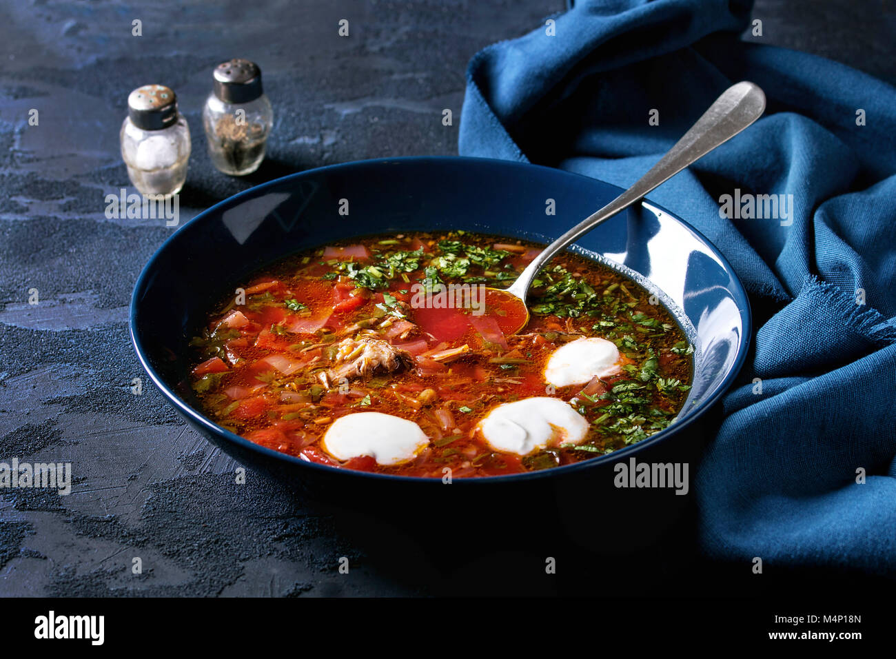 Plate of traditional beetroot borscht soup with sour cream and fresh coriander served with garlic bread buns pampushka - Stock Image