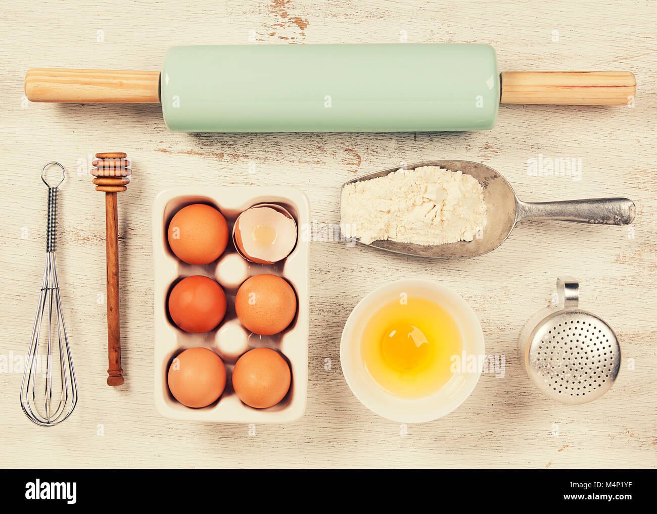 Baking Tools And Ingredients   Flour, Rolling Pin, Eggs, Measuring Spoons  On Vintage Wood Table. Top View. Rustic Background With Free Text Space