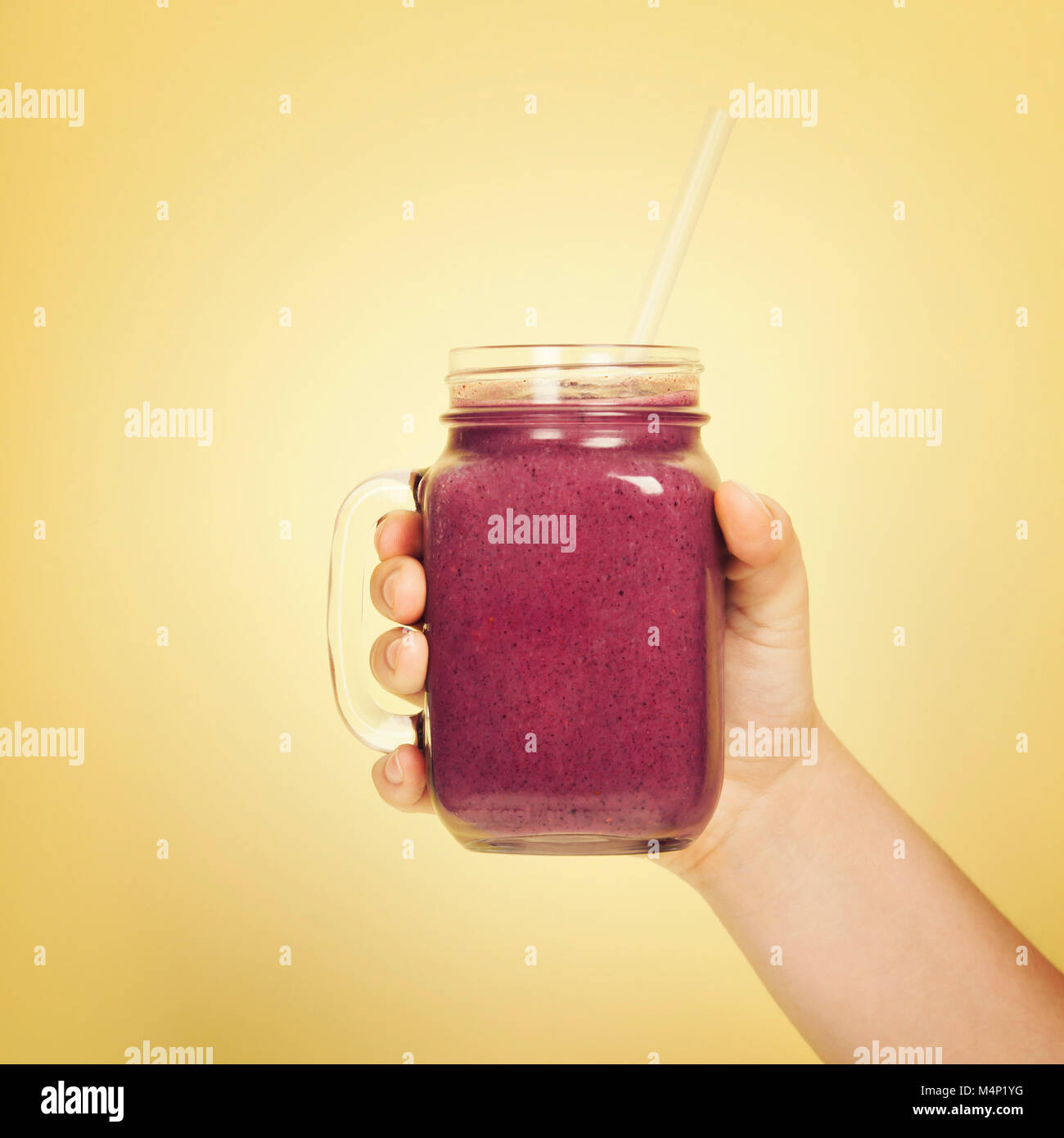 Womans hand holding smoothie shake against bright wall. Drinking  healthy smoothie concept Stock Photo