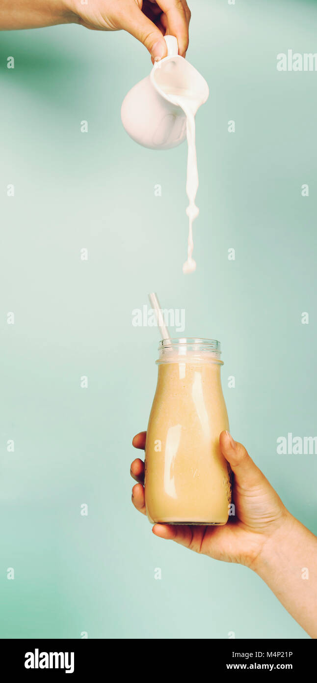 Womans hand holding smoothie shake against bright wall. Pouring milk into smoothie. Drinking healthy smoothie concept Stock Photo