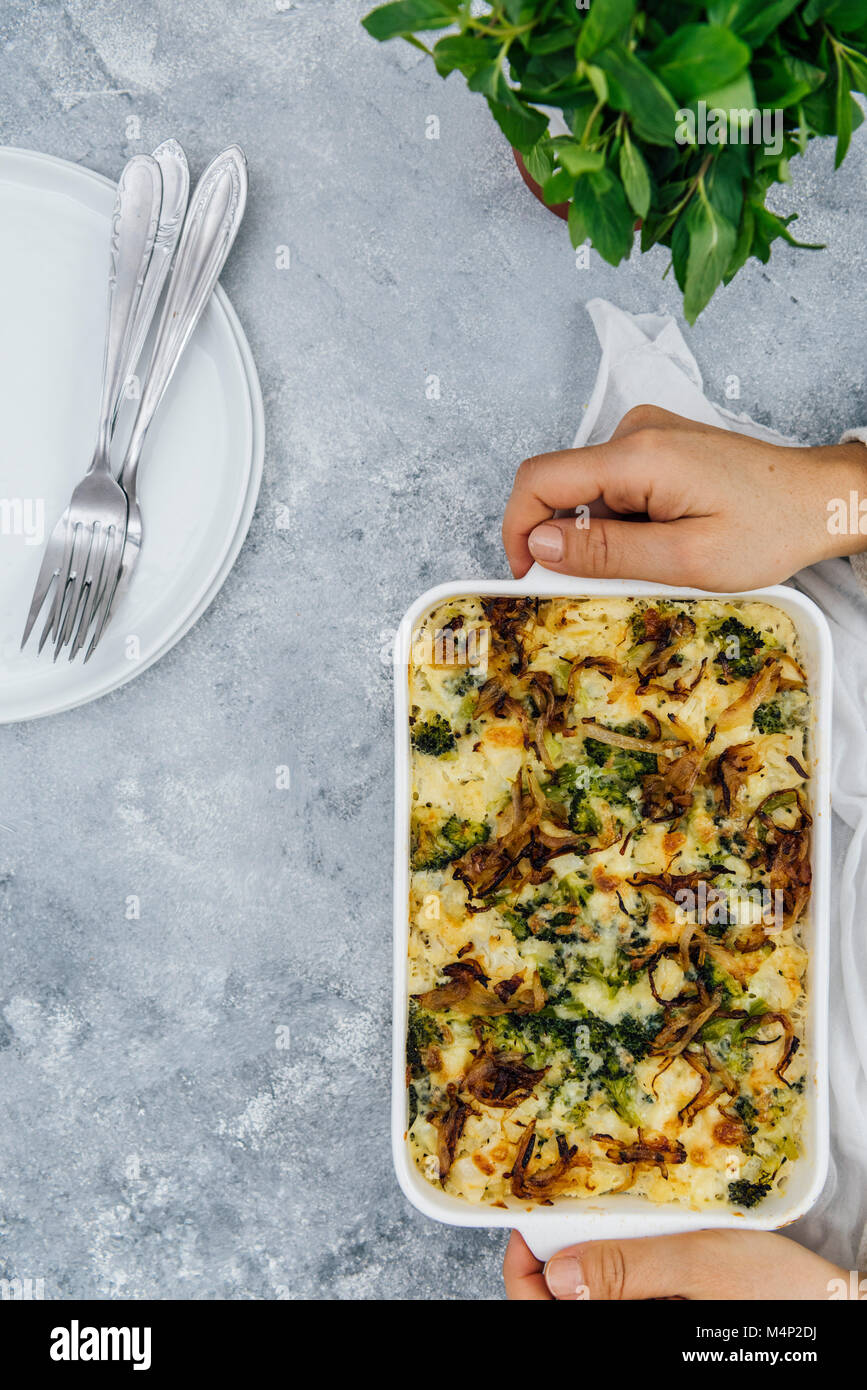 A woman serving a vegetarian cauliflower and broccoli casserole in a pan photographed from top view. Fresh herbs, - Stock Image