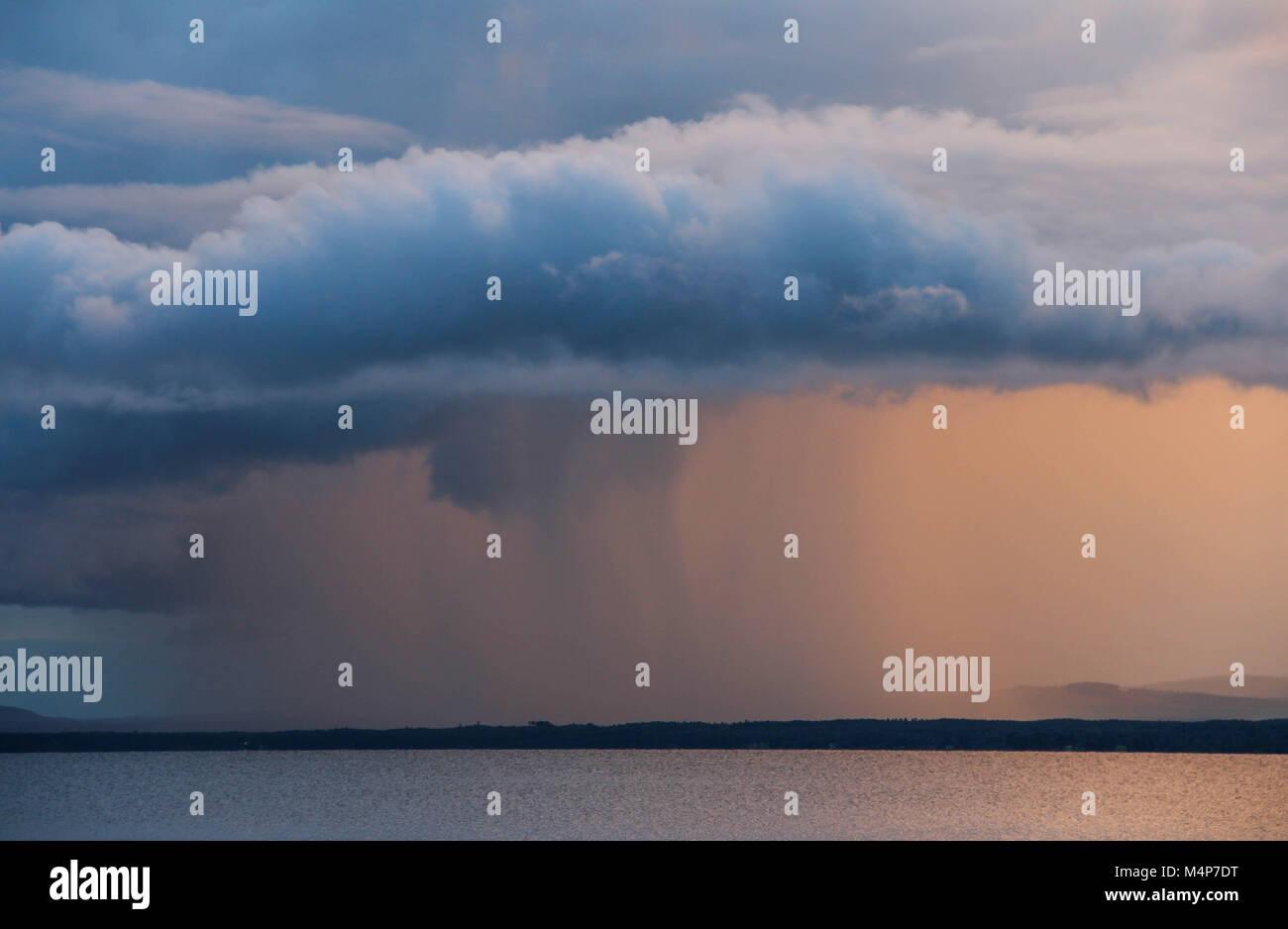 Rain cloud at sunset over Orsa lake in Dalarna, Swden. - Stock Image
