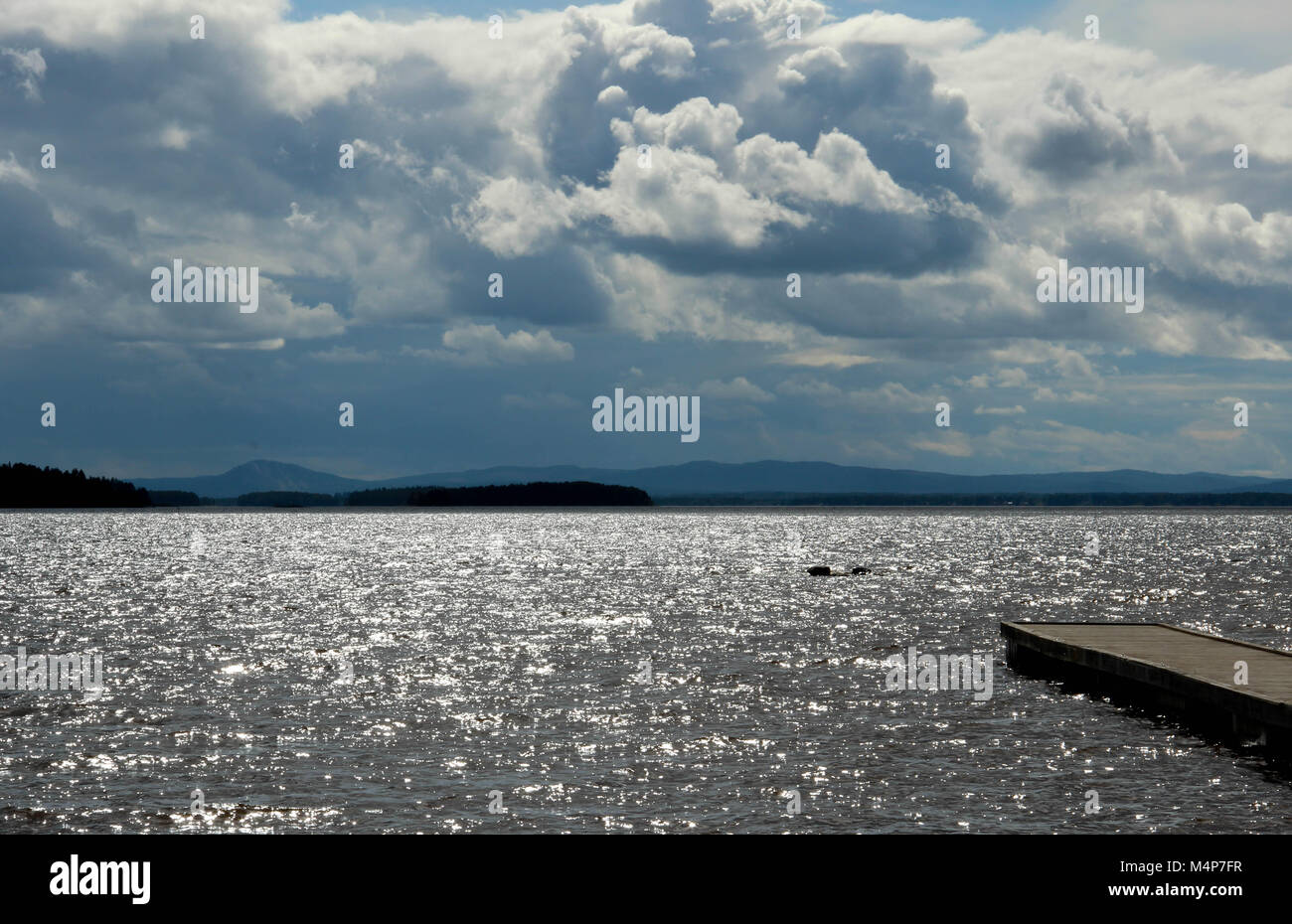 A bridge in a big lake with glittering waves, and mountains in the background. - Stock Image