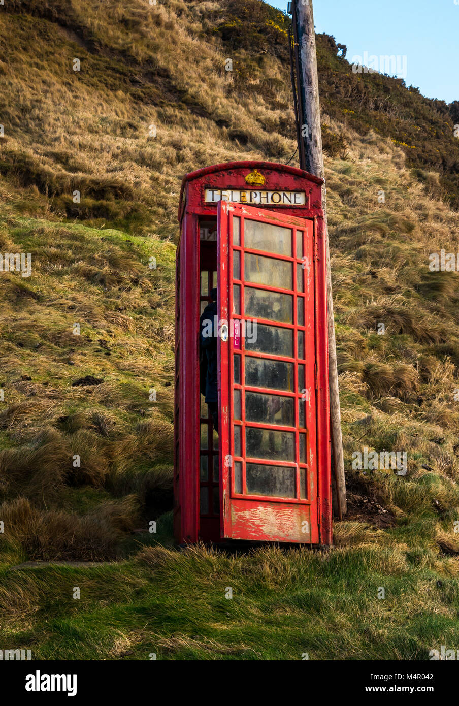 Old neglected Brisith red telephone box, still in working order in small seaside village, Crovie, Aberdeenshire, - Stock Image