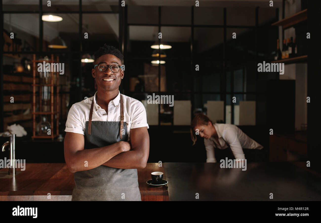 Man standing in his coffee shop with arms crossed while woman is working in the background. Young entrepreneurs - Stock Image