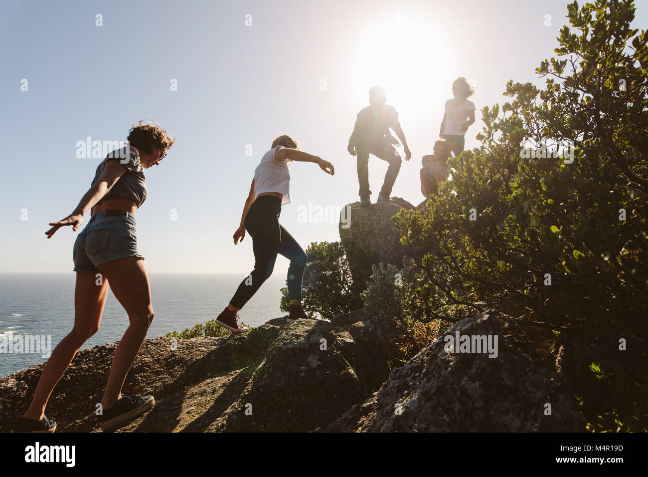 Group of friends on a mountain. Young people on mountain hike on a summer day. Men and women climbing rocks. - Stock Image