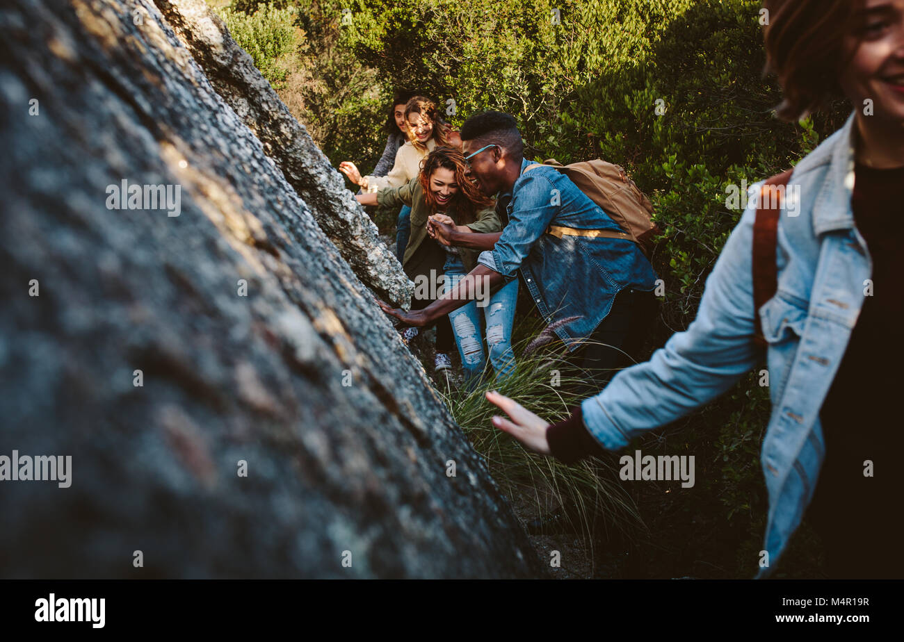 Young men and women walking through a mountain trail. Young people hiking in mountain. Stock Photo