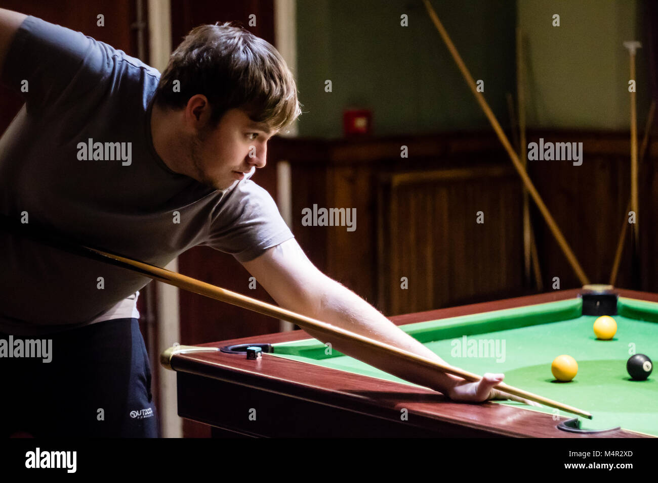 A man preparing to play a pool shot, taken from the side - Stock Image