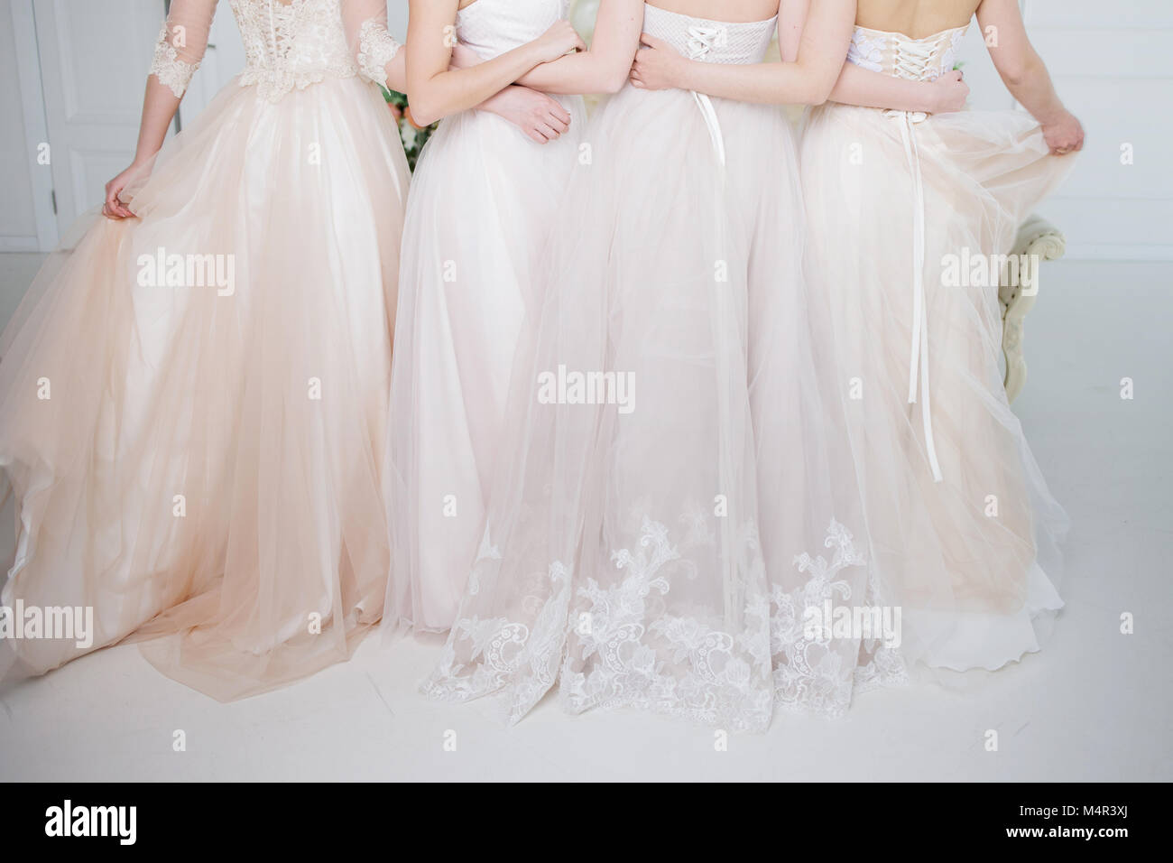 Bride in wedding salon. Four beautiful girl are in each other's arms. Close-up lace skirts - Stock Image