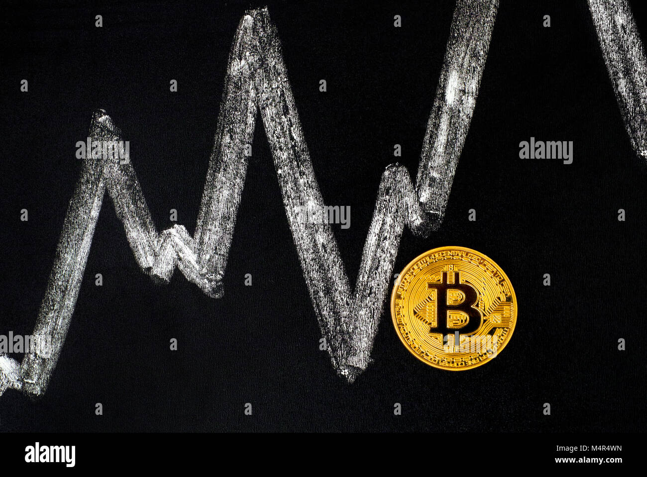 Golden Bitcoin coin on blackboard with chalk drawing graph. - Stock Image