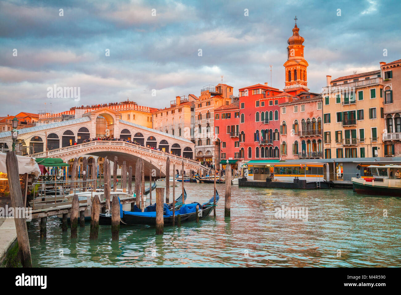Classic panoramic view with traditional Gondolas on famous Canal Grande with famous Rialto Bridge in the background - Stock Image