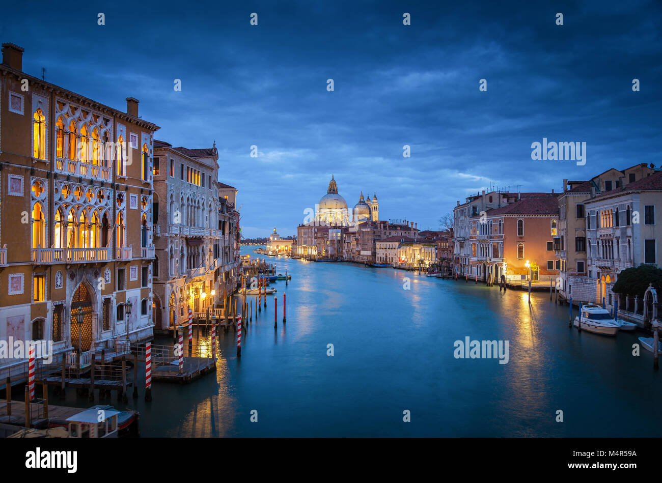 Classic view of famous Canal Grande with historic Basilica di Santa Maria della Salute in the background in twilight, - Stock Image