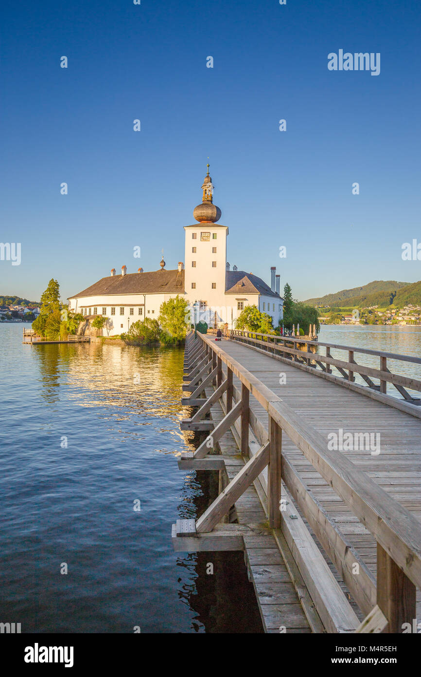 Beautiful view of famous Schloss Ort with wooden bridge at Lake Traunsee in beautiful golden evening light at sunset, - Stock Image