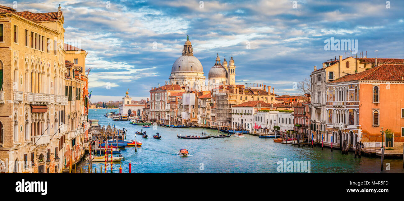 Classic panoramic view of famous Canal Grande with Basilica di Santa Maria della Salute in beautiful golden evening - Stock Image