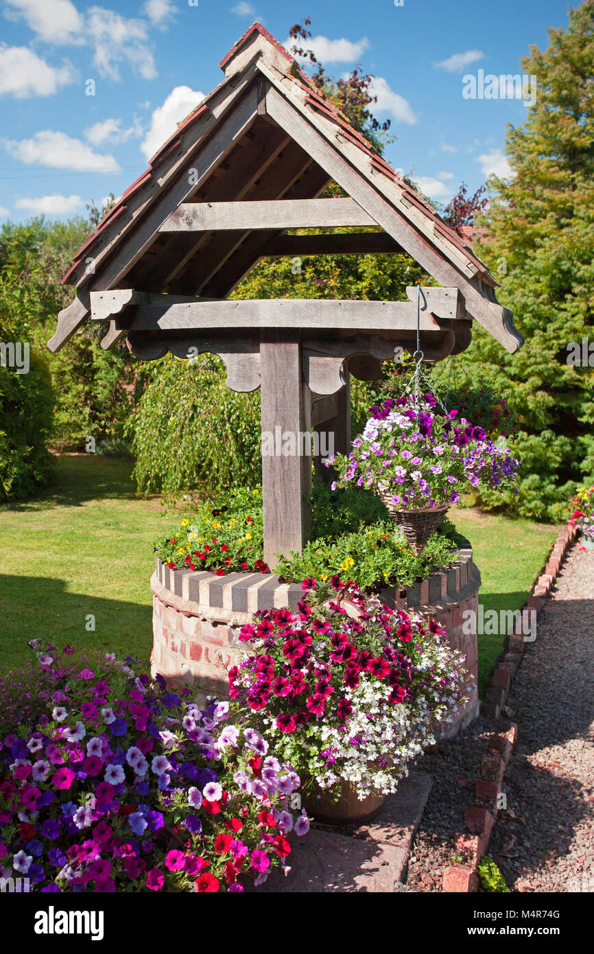 Old garden well planted with mixed petunias and calibrachoa - Stock Image