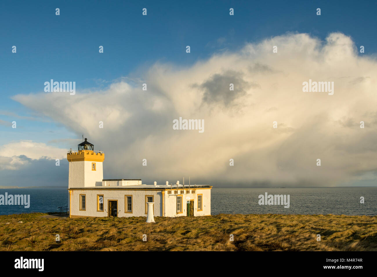 Duncansby Head lighthouse with a cumulonimbus shower cloud behind. Duncansby Head, near John o'Groats, Caithness, - Stock Image