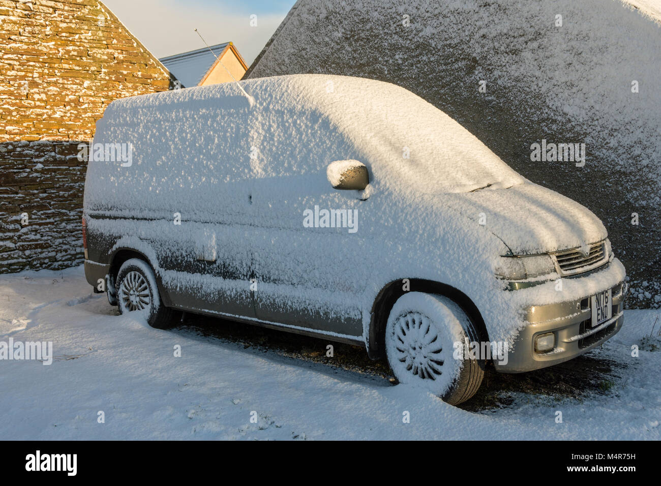 A Mazda Bongo motor vehicle plastered with snow at the village of Mey, Caithness, Scotland, UK. - Stock Image