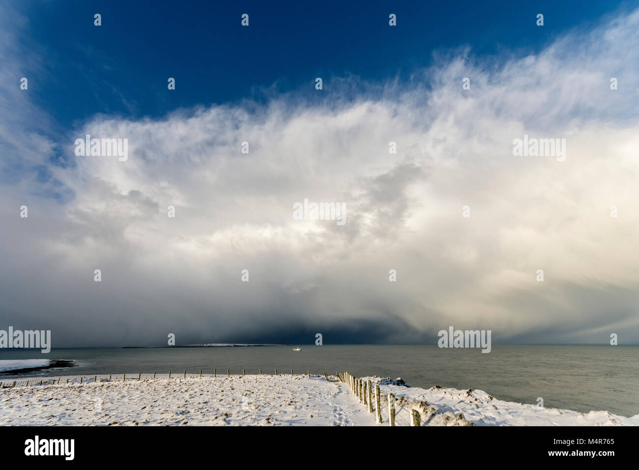 Heavy snow shower approaching the island of Stroma and a fishing boat, looking over the Pentland Firth from Duncansby - Stock Image