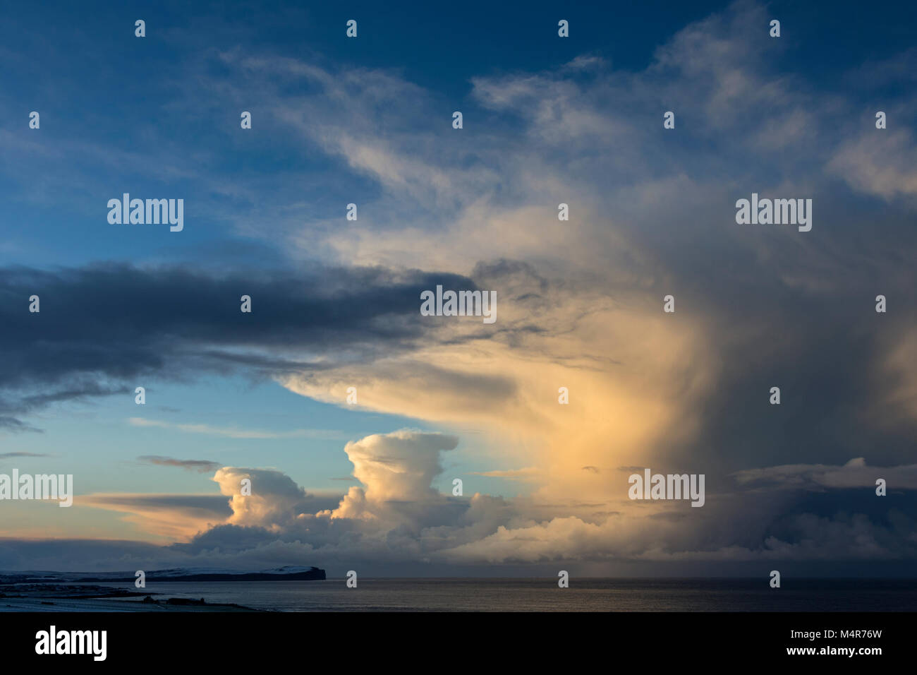 Cumulonimbus cloud near sunset over Dunnet Head and the Pentland Firth, from near St. John's Point, Caithness, - Stock Image