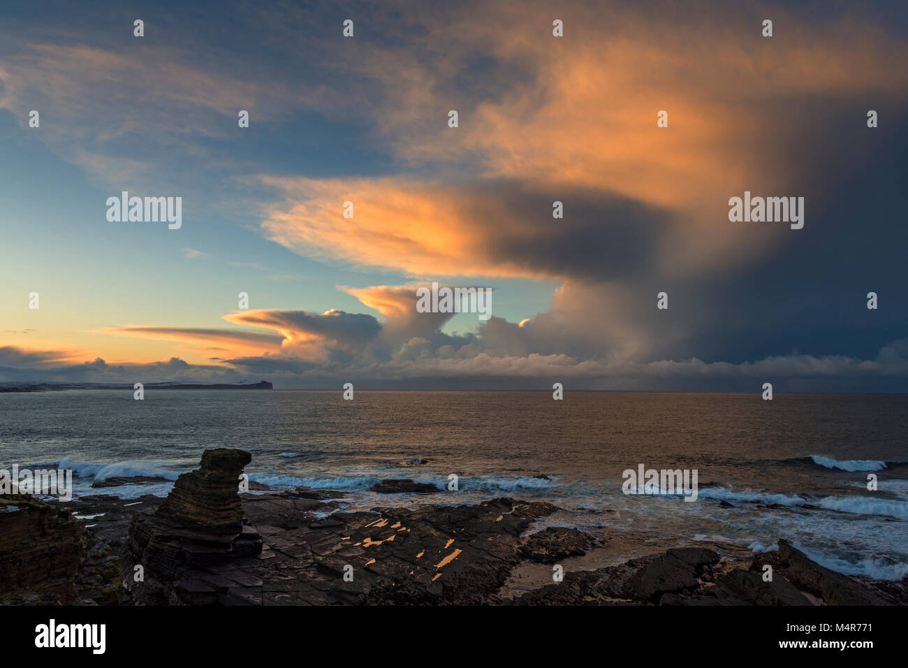 Cumulonimbus cloud at sunset over Dunnet Head and the Pentland Firth, from one of the Men of Mey sea stacks, St. - Stock Image