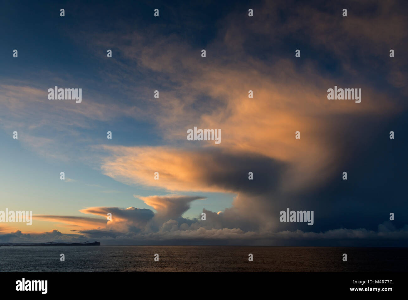 Cumulonimbus cloud at sunset over Dunnet Head and the Pentland Firth, from St. John's Point, Caithness, Scotland, - Stock Image