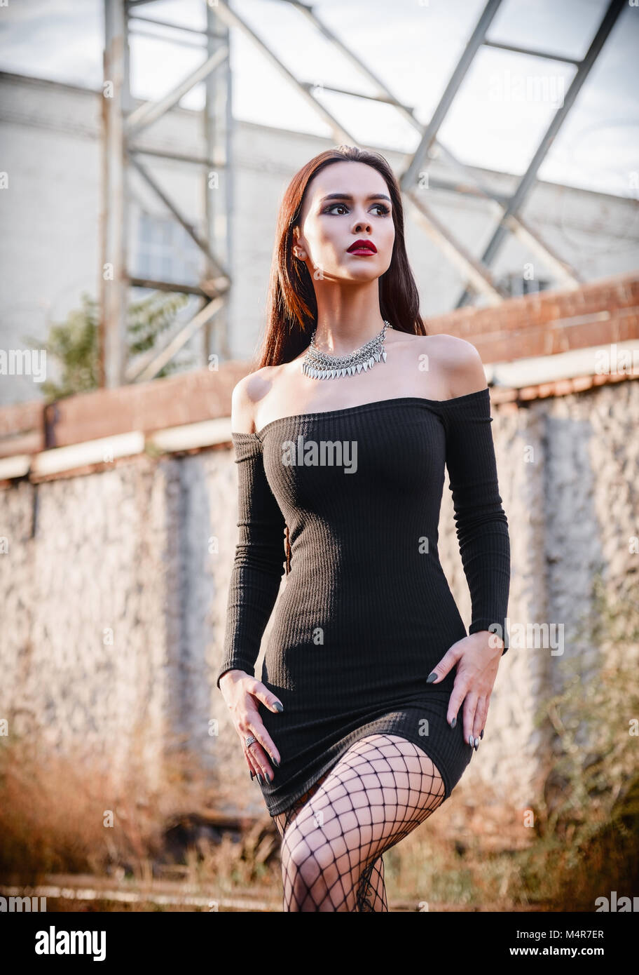 Portrait of the beautiful goth girl (informal model) in black dress and tights standing in industrial area - Stock Image