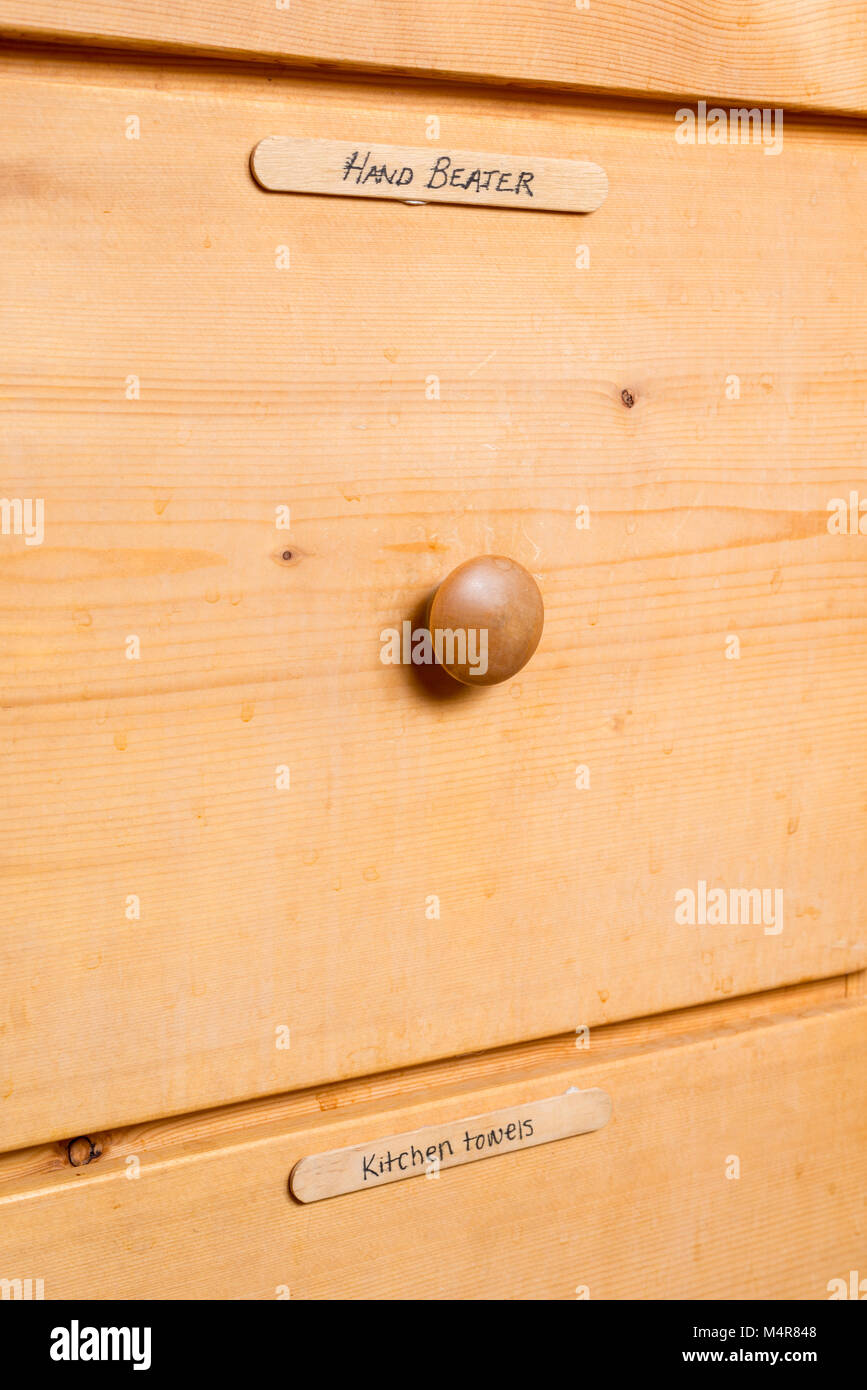 Kitchen drawers with tounge depressor labels. - Stock Image