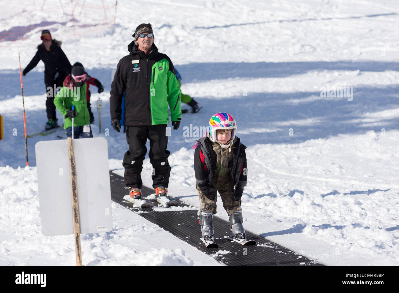 Kids and ski instructor on a magic carpet ski lift at Anthony Lakes Mountain Resort in Northeast Oregon. - Stock Image