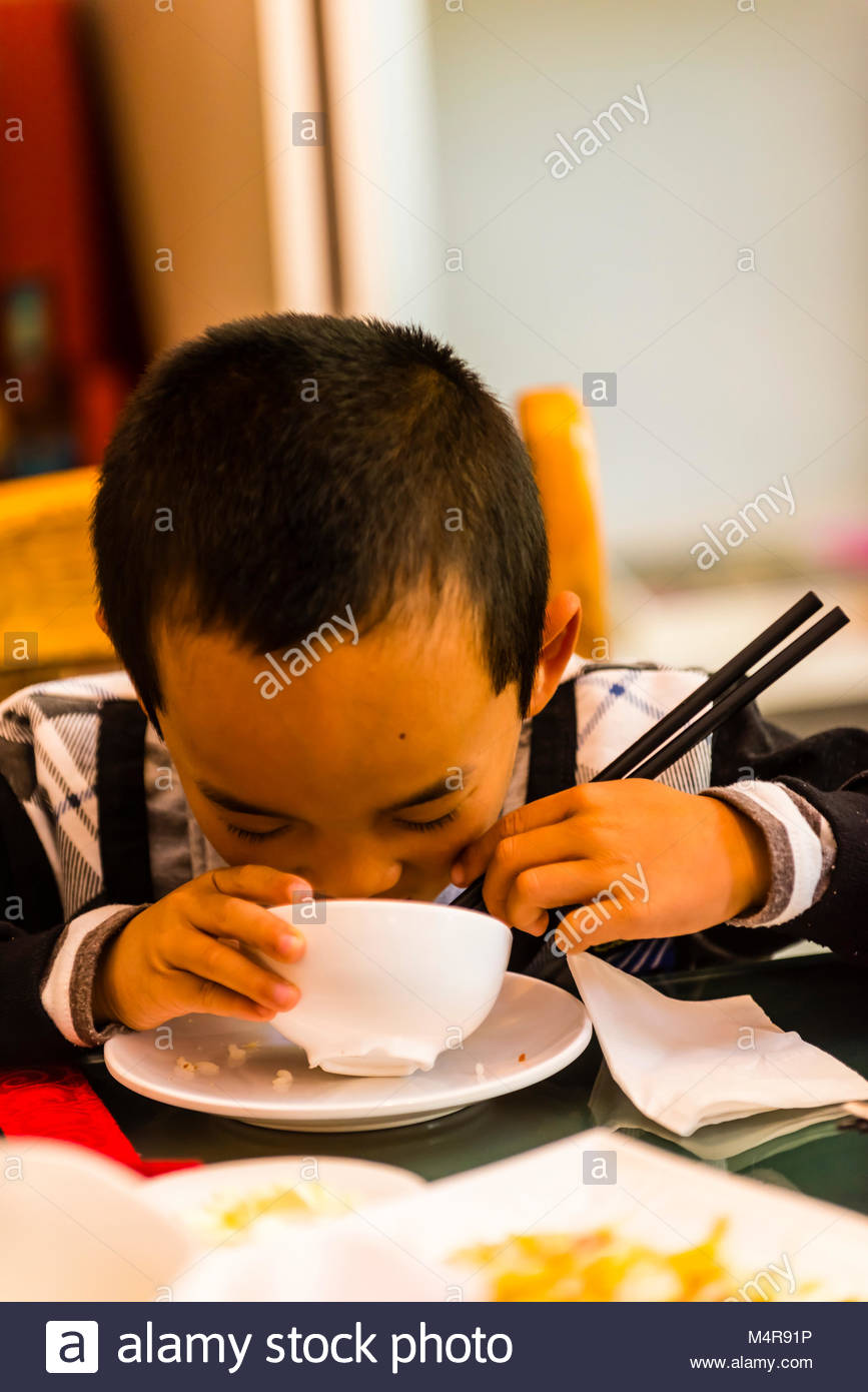 A boy eating lunch with his family at Mishi Restaurant, Lijiang, Yunnan Province, China. - Stock Image
