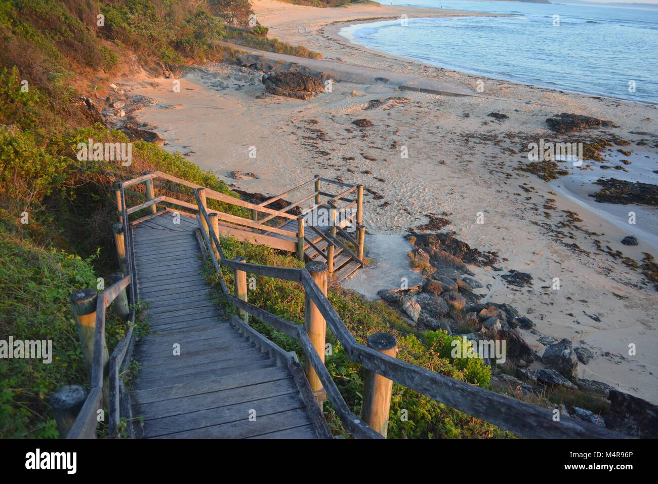 Morning sunlight falls upon the wooden steps leading from Bonville Headland down to Rocks and Sawtell Beach, NSW - Stock Image