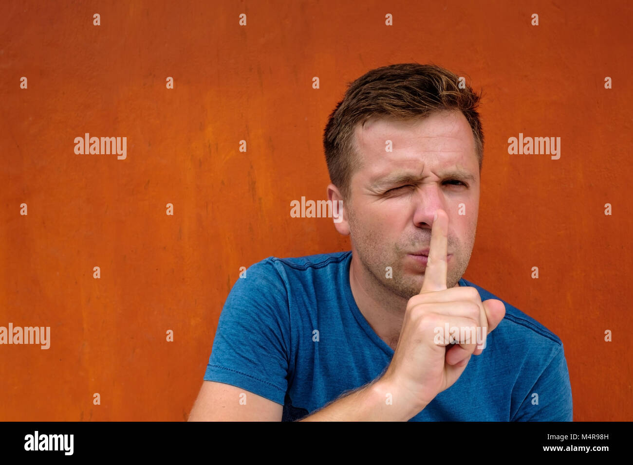 Closeup portrait of young caucasian man placing finger on lips as if to say, shh, be quiet - Stock Image