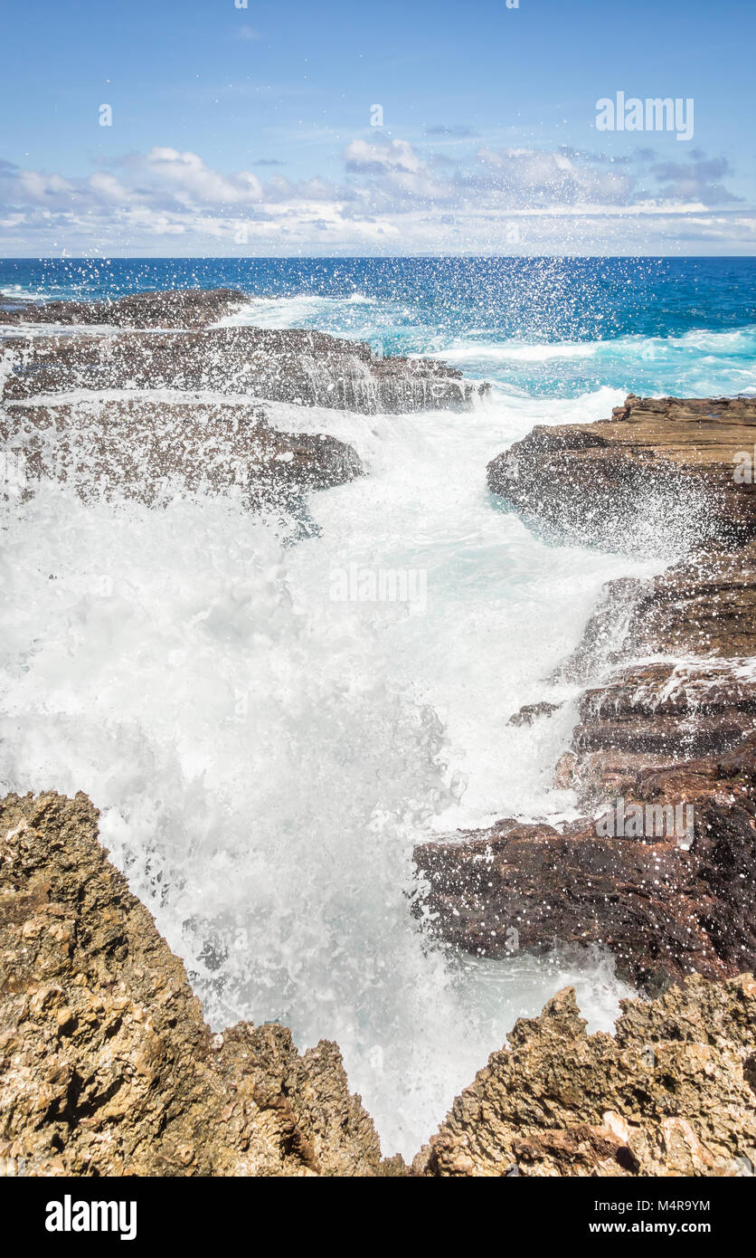 Large waves smashing through a sharp, rocky inlet on the coastline of the eastern side Oahu, Hawaii. - Stock Image