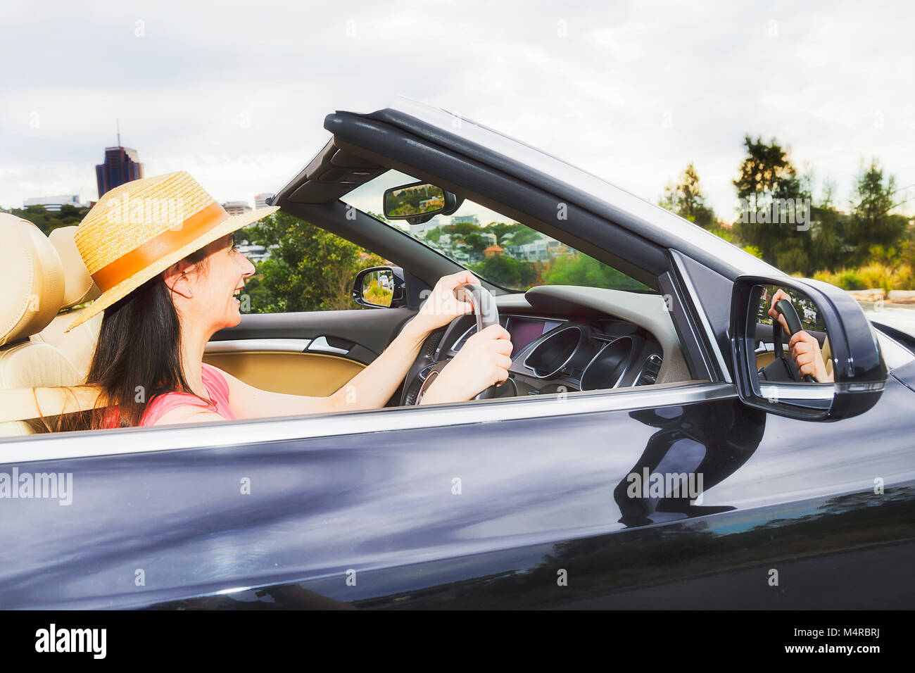 Close side view of young lady driver in an open modern sports convertible car with soft top folded down against - Stock Image