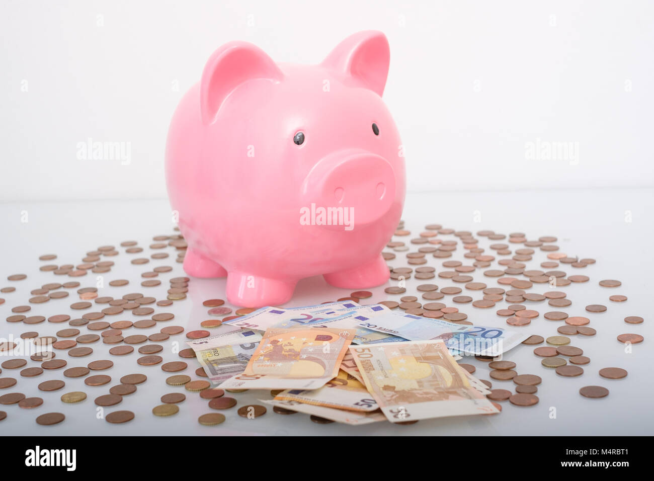 Savings concept. Pink piggy bank and coins isolated on white background - Stock Image