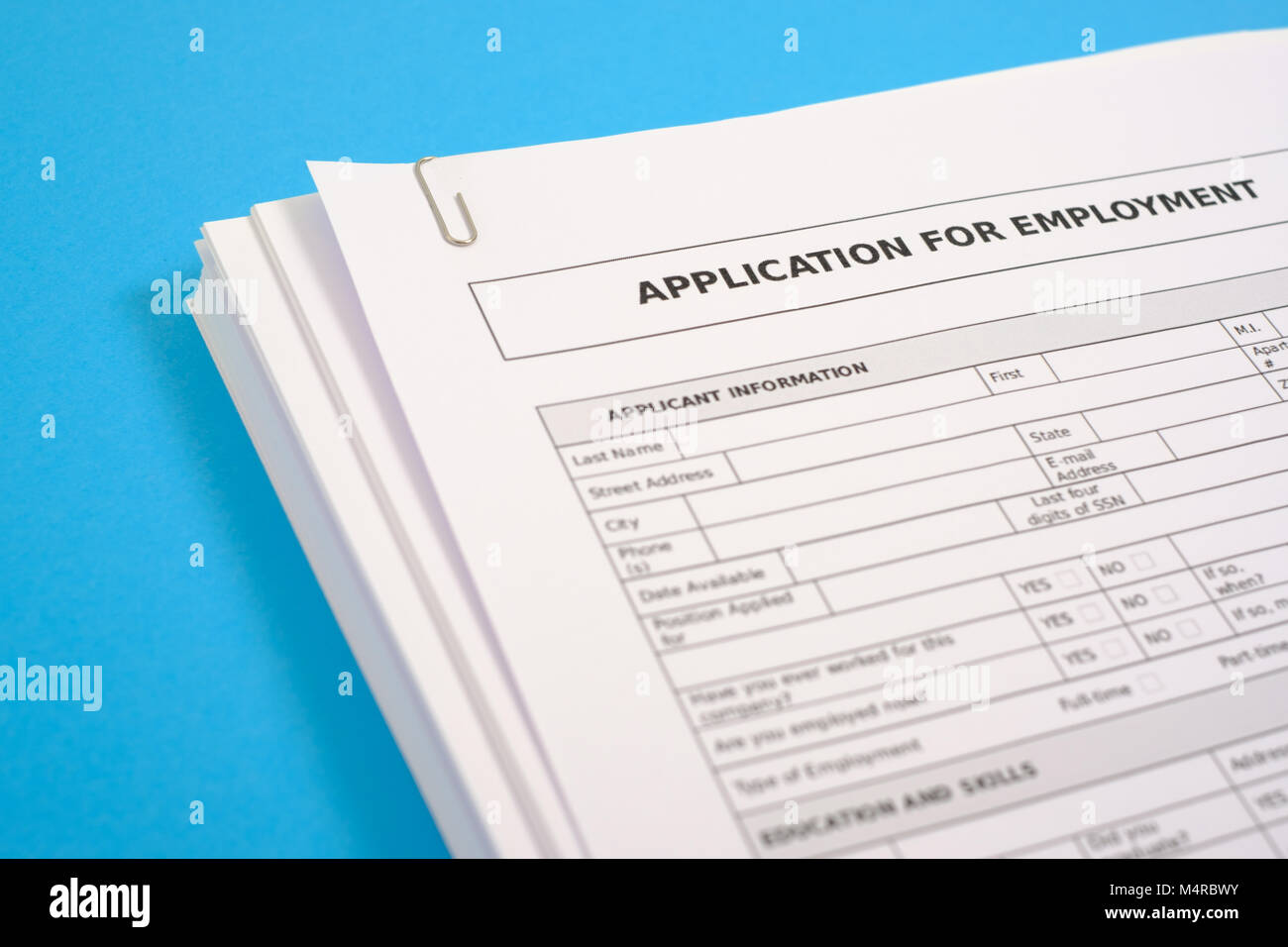 Stack of cv and application for employment on blue desk - Stock Image