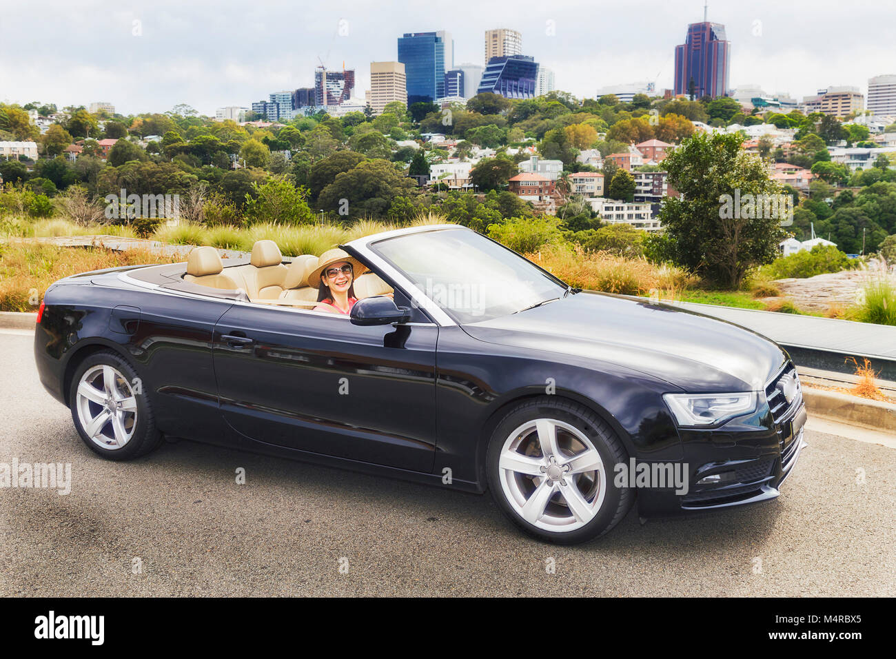 Side view of small convertible luxury roadster car with young lady driver in front of modern North Sydney CBD on - Stock Image