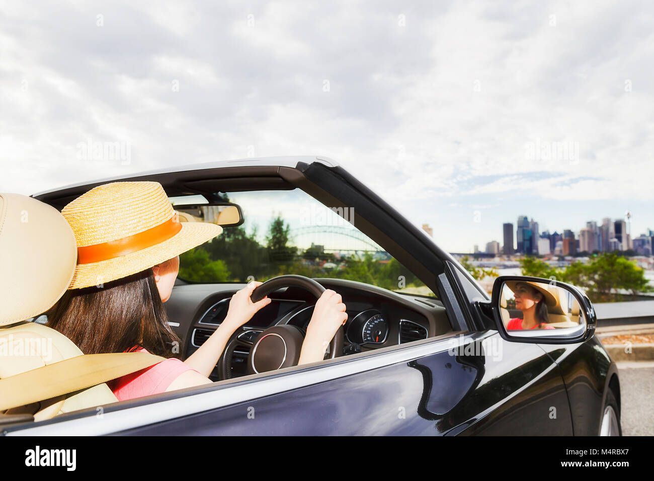 Attractive young successful woman drives a modern small passenger convertible roadster car on streets of Sydney - Stock Image