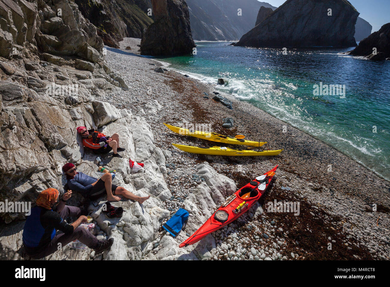 Sea kayakers relaxing on a storm beach beneath Slieve Tooey, County Donegal, Ireland. - Stock Image