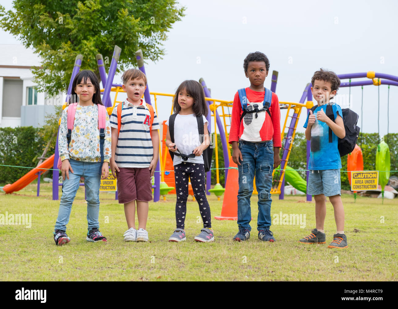 group of diversity school children playing at playground in kindergarten preschool.back to school - Stock Image