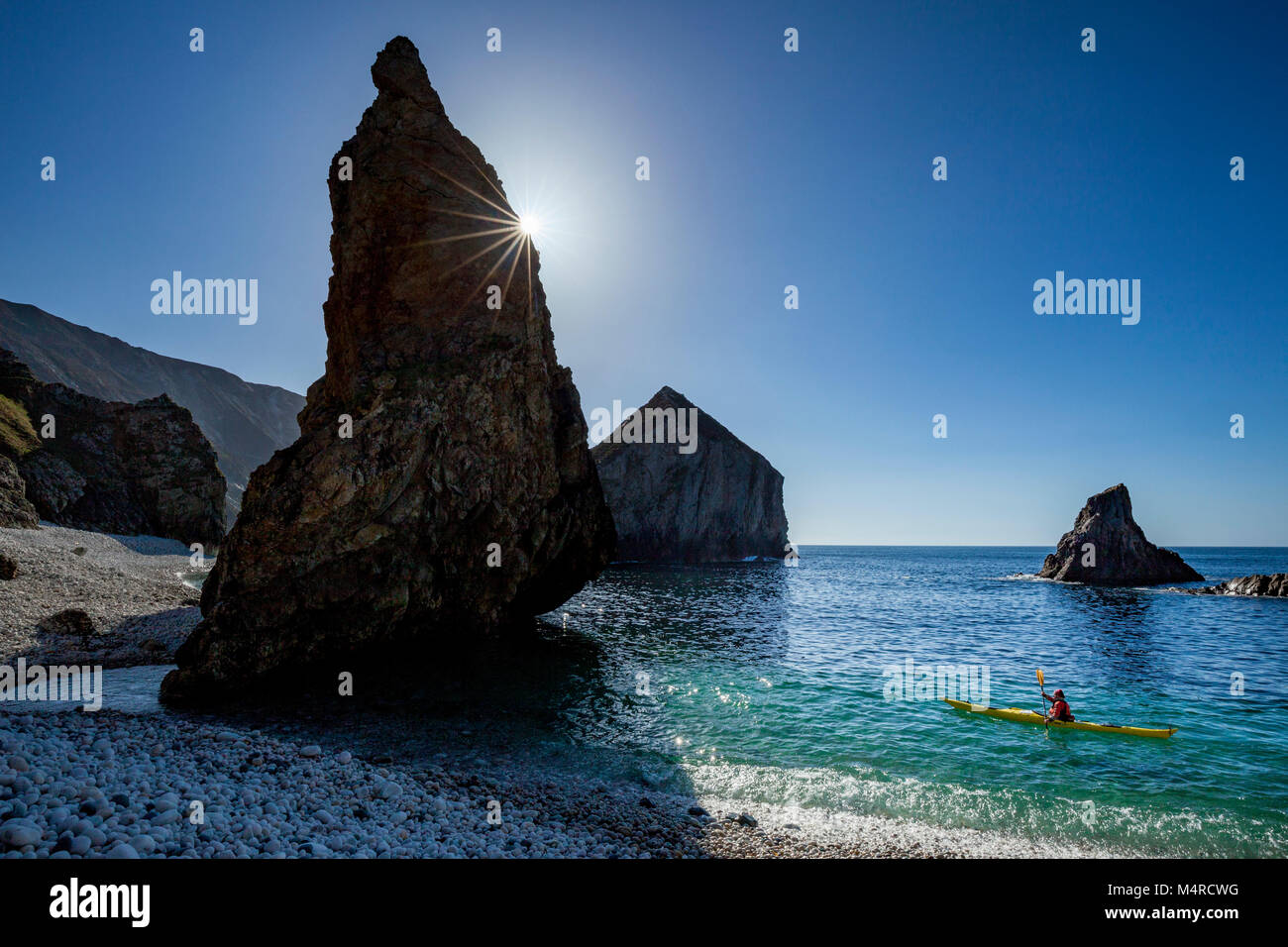 Sea kayaking beside stacks and pinnacles beneath Slieve Tooey, County Donegal, Ireland. - Stock Image