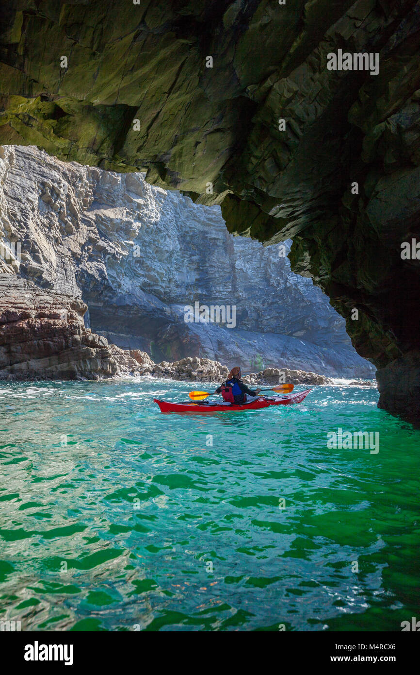 Sea kayaker exploring a cave near Glencolmcille, County Donegal, Ireland. - Stock Image