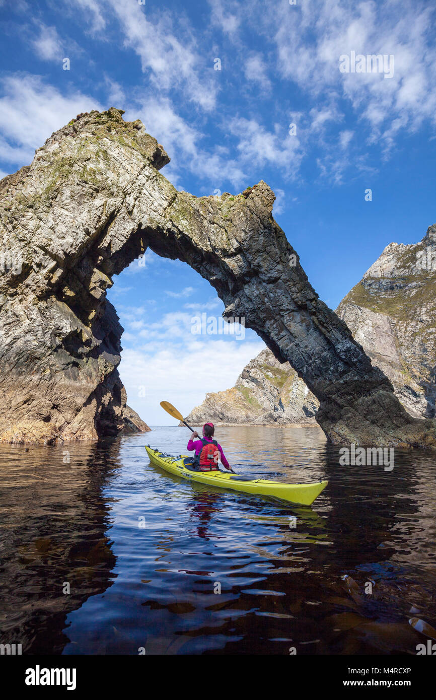 Sea kayaking beneath a natural arch near Sturrall, Glencolmcille, County Donegal, Ireland. - Stock Image