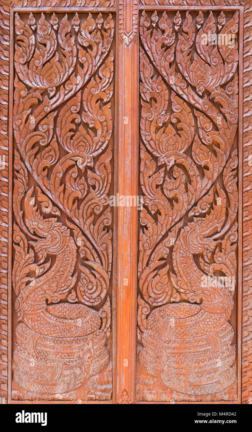 Carving pattern with the dragon symbol in the traditional Thai style on the wooden door of the Thai church. & Carving pattern with the dragon symbol in the traditional Thai style ...
