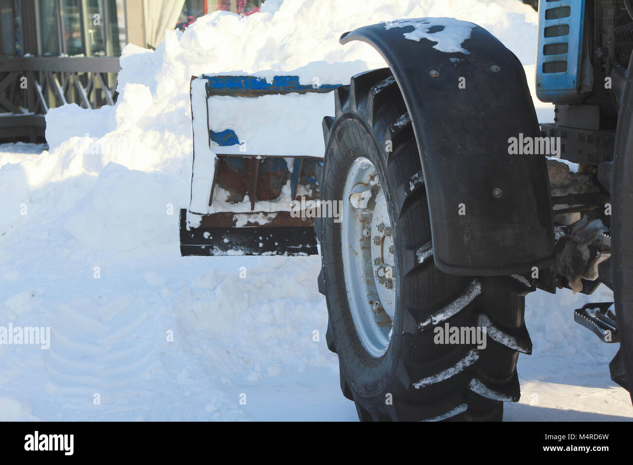 Clearing snow from the road with bulldozer in the city in winter, focus on blade and wheel - Stock Image