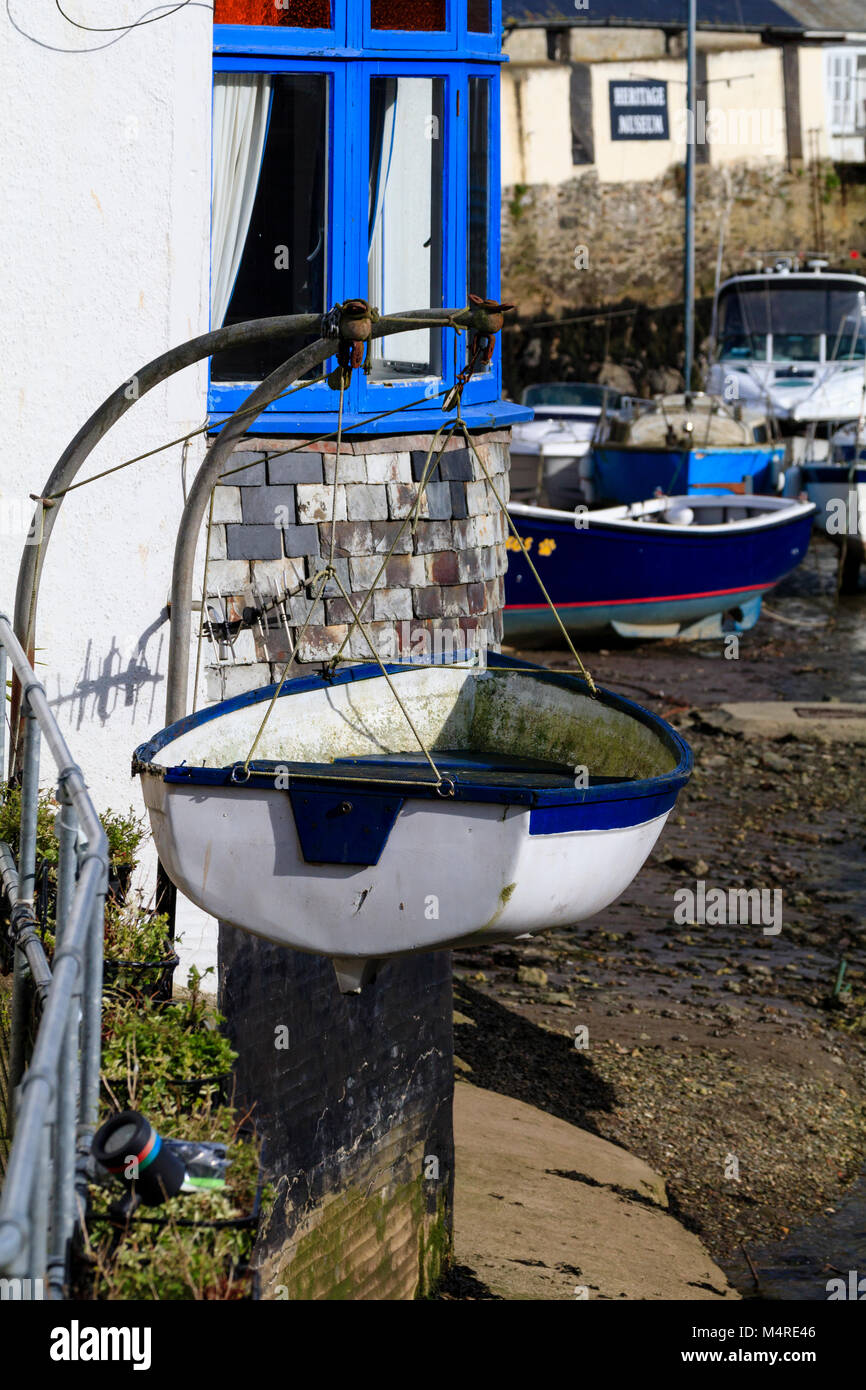 Blue and white dinghy on davits contrasts with the painted house walls at the harbourside in Polperro, Cornwall, - Stock Image